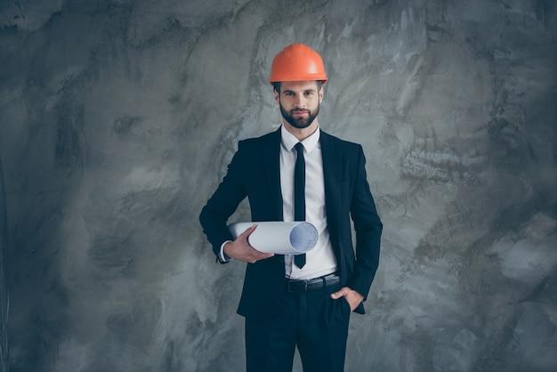 Ritratto di serio uomo alla moda appaltatore tenere blueprint pronto a gestire enorme costruzione industriale indossare pantaloni smoking smoking nero pantaloni giacca blazer isolato su parete di colore grigio