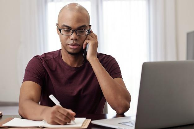 Ritratto di giovane uomo d'affari serio che chiama sul telefono e che prende appunti nel pianificatore quando parla al telefono con il cliente