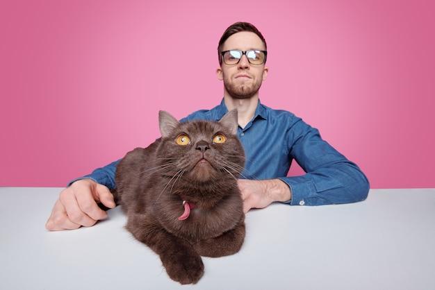 Ritratto del proprietario serio del gatto giovane seduto al tavolo con animale domestico marrone