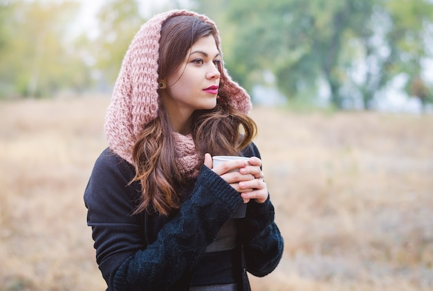 Ritratto di una giovane ragazza seria con una tazza di caffè (tè), una sciarpa in autunno parco.