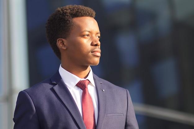 Ritratto di grave giovane imprenditore offeso in abito formale in piedi all'aperto. uomo arrabbiato afroamericano africano nero. foto del profilo al giorno pieno di sole