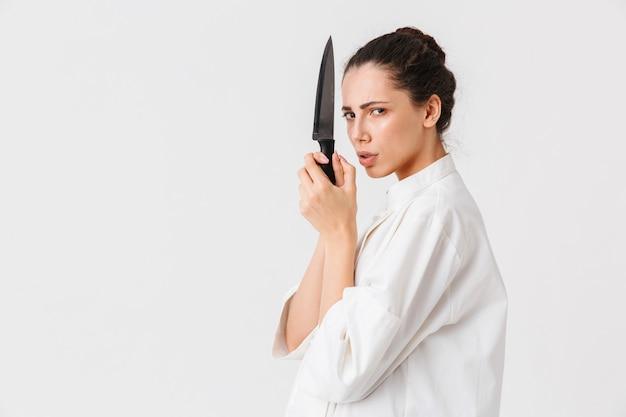 Ritratto di una giovane donna seria con utensili da cucina
