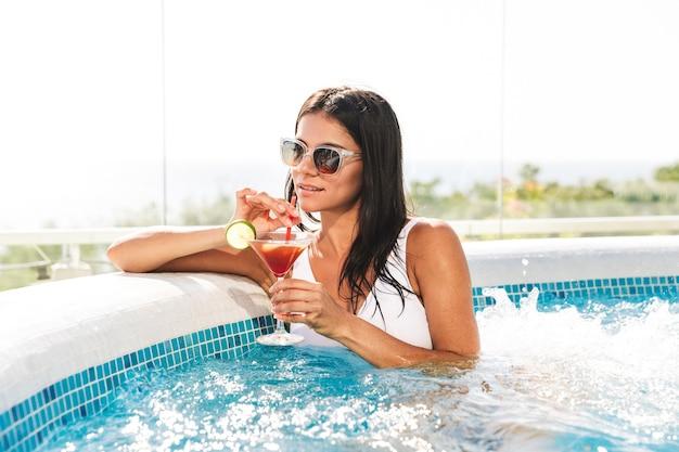 Ritratto di donna europea sessuale in costume da bagno bianco e occhiali da sole, prendere il sole e bere cocktail in piscina durante le vacanze