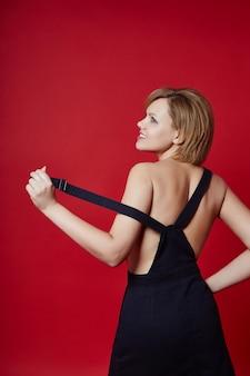 Ritratto di una donna bionda adulta sexy su una parete scura. fiduciosa donna d'affari con i capelli corti