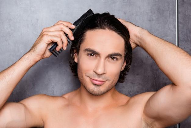 Ritratto del giovane bello sexy che pettina i suoi capelli