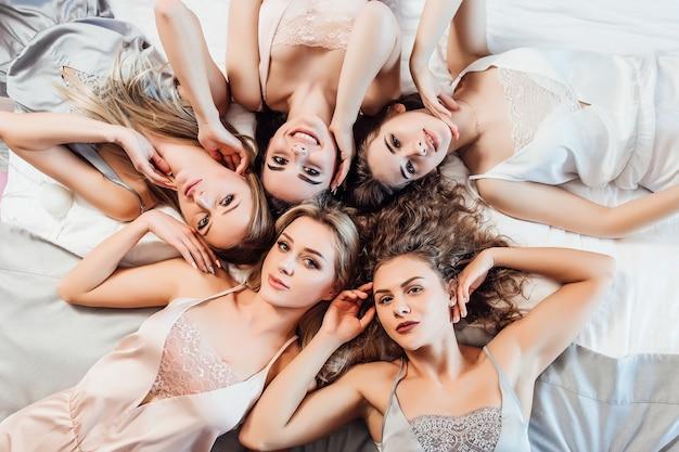 Ritratto di ragazze sexy, carine, affascinanti, divertenti, sciocche e allegre in abiti da notte sdraiate sul letto