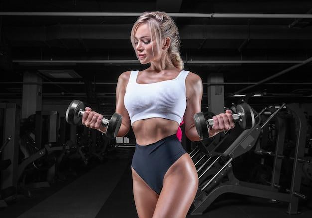Ritratto di una sportiva sexy in posa in palestra con manubri. concetto di fitness.