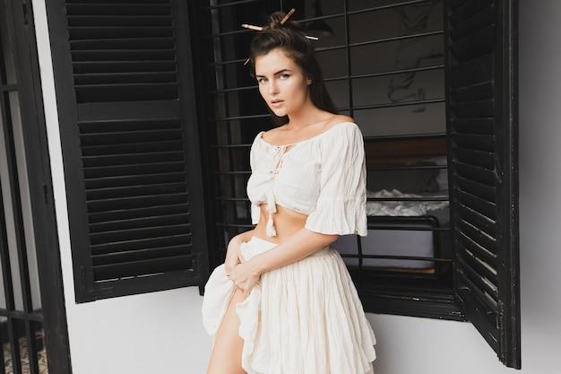 Ritratto di donna sexy con acconciatura alla moda che indossa abiti in tessuto naturale