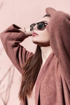 Ritratto sexy giovane donna splendida in occhiali da sole alla moda in cappotto alla moda con belle labbra sulla strada in giornata di sole. modello adorabile della ragazza in vestiti alla moda che posano nel giorno di luce solare di primavera in città.