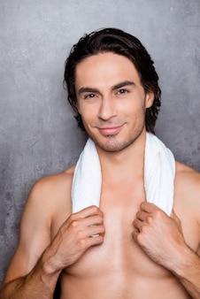 Ritratto di giovane uomo sorridente sexy che tiene un asciugamano bianco sul collo