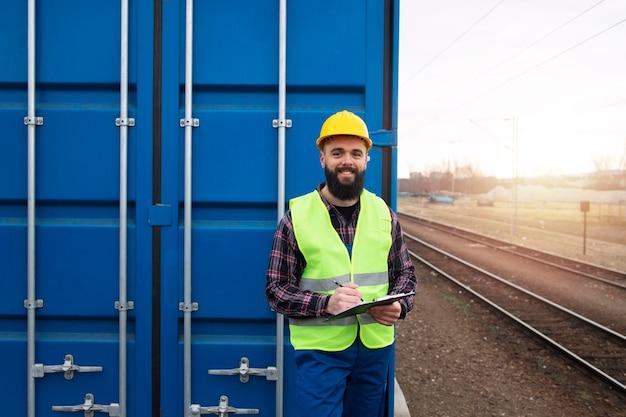 Ritratto del caposquadra dell'operaio di spedizione che fa una pausa il container alla stazione dei treni merci.