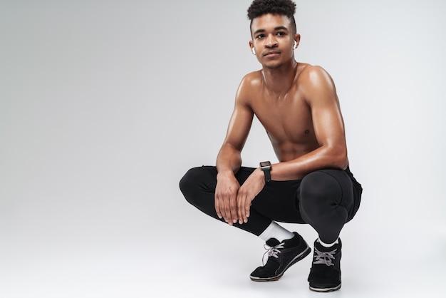 Ritratto di uomo afroamericano a torso nudo che usa auricolari mentre si accovaccia isolato su grigio