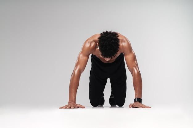 Ritratto di uomo afroamericano senza camicia che usa auricolari e fa esercizio mentre si allena isolato su grigio