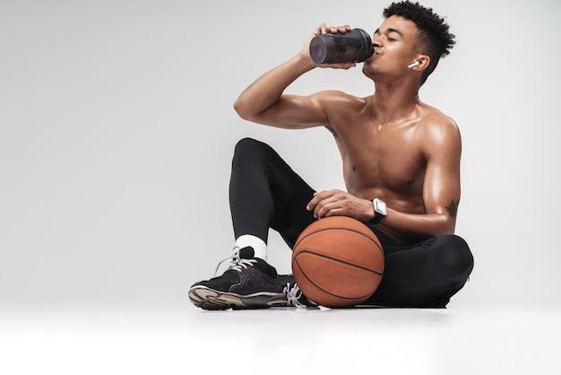 Ritratto di uomo afroamericano senza camicia che usa auricolari e acqua potabile mentre è seduto sul pavimento isolato su bianco
