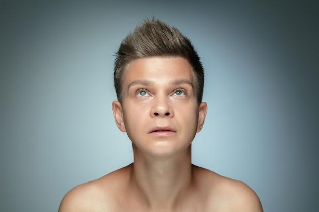 Ritratto di giovane senza camicia isolato sul muro grigio. modello maschio sano caucasico che osserva in su e che propone. concetto di salute e bellezza maschile, cura di sé, cura del corpo e della pelle.