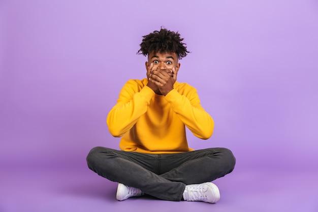 Ritratto di un ragazzo afroamericano scioccato seduto sul pavimento con le gambe incrociate e che copre la bocca con le mani, isolato su sfondo viola