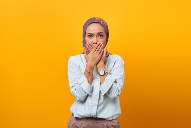 Ritratto di una donna asiatica scioccata mentre copre la bocca con le mani su sfondo giallo