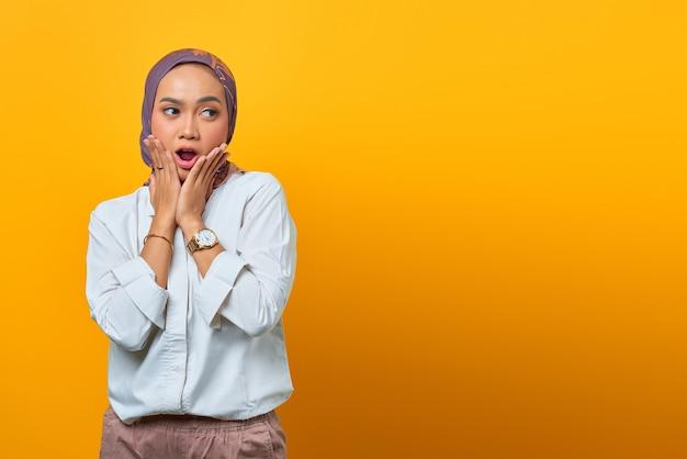 Ritratto di donna asiatica scioccata con la bocca aperta e guardando di lato su sfondo giallo