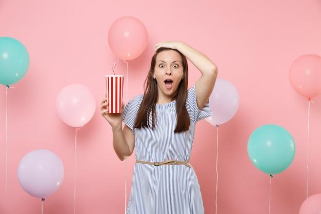 Ritratto di giovane e bella donna scioccata che indossa un abito blu aggrappato alla testa tenendo una tazza di plastica di cola o soda su sfondo rosa pastello con mongolfiere colorate. concetto di festa di compleanno.