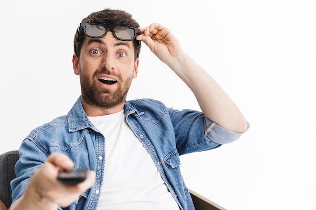 Ritratto di un bell'uomo barbuto scioccato che indossa abiti casual seduto su una sedia isolato, guardando un film