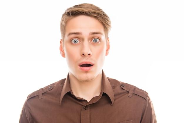 Ritratto di giovane uomo d'affari triste scioccato con la bocca aperta