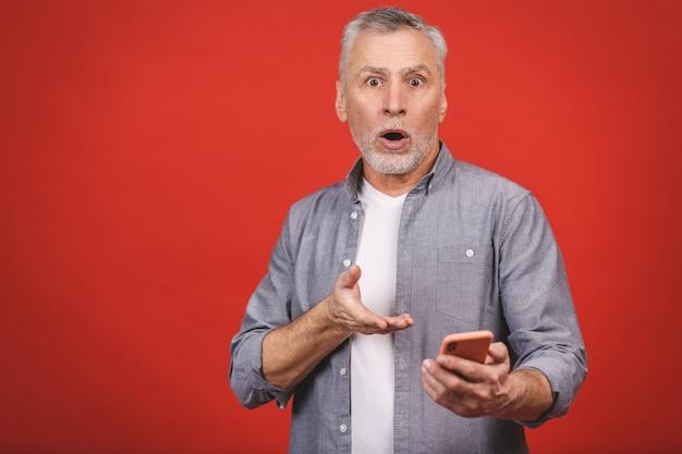 Ritratto dell'uomo senior colpito nella bocca d'apertura casuale ansimante dalla preoccupazione e dalla sorpresa che tiene telefono cellulare, guardante in camera isolato sopra la parete rossa.