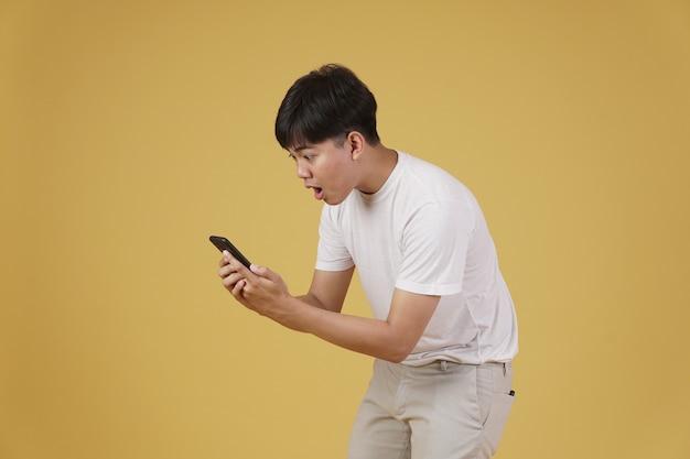Il ritratto del giovane asiatico eccitato sorpreso scioccato si è vestito con indifferenza guardando il telefono astuto mobile isolato