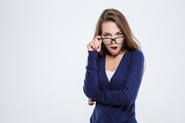 Ritratto di una donna scioccata che guarda la telecamera isolata su uno sfondo bianco
