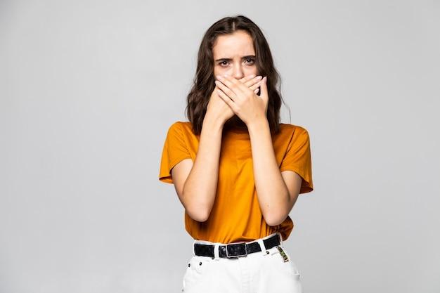 Ritratto di donna scioccata con la bocca aperta che guarda lontano isolata su uno sfondo grigio