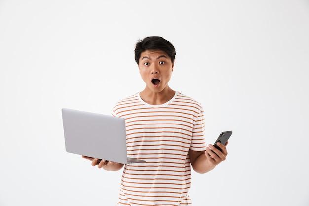 Ritratto di un giovane uomo asiatico scioccato che tiene il computer portatile