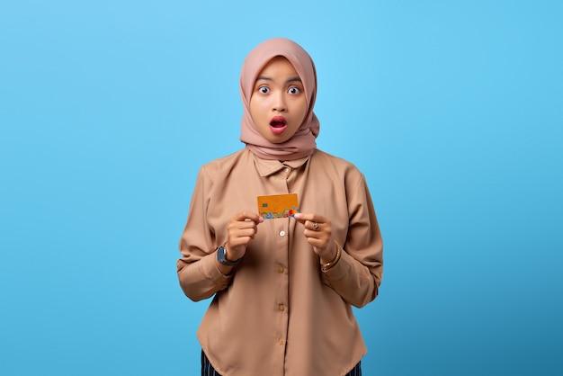 Ritratto di una giovane donna asiatica scioccata che tiene in mano una carta di credito mentre guarda la telecamera