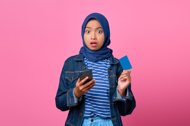 Ritratto di una giovane donna asiatica scioccata che tiene in mano uno smartphone mentre mostra la carta di credito