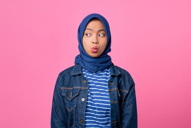 Ritratto di una giovane donna asiatica scioccata che guarda di lato su sfondo rosa