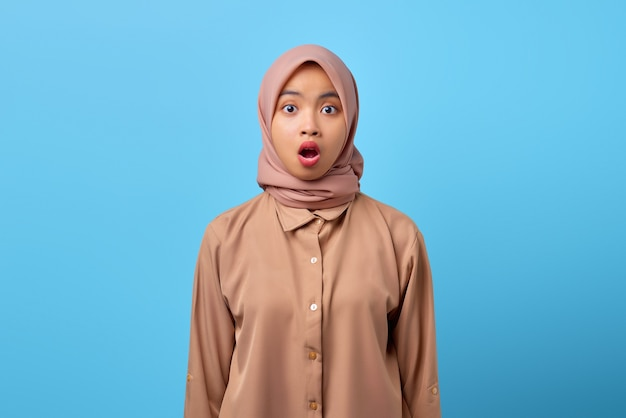 Ritratto di una giovane donna asiatica scioccata con la bocca aperta che indossa l'hijab su sfondo blu