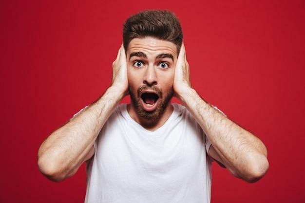 Ritratto di un giovane uomo barbuto scioccato coprire le orecchie