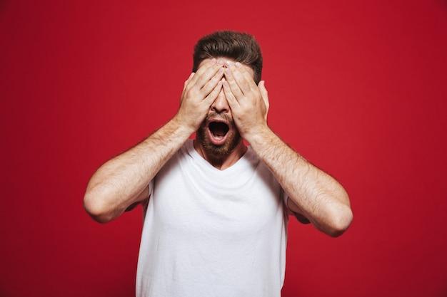 Ritratto di un fronte di copertura giovane uomo barbuto scioccato