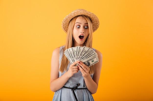 Ritratto di una giovane donna bionda scioccata in cappello estivo