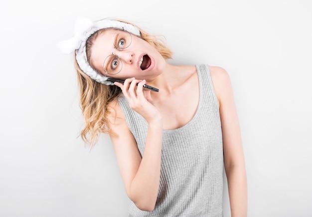 Ritratto di una giovane ragazza scioccata utilizzando il cellulare