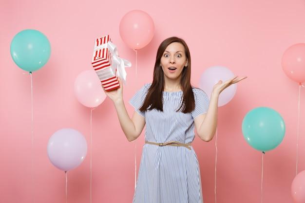 Ritratto di giovane donna scioccata in abito blu che allarga le mani tenendo una scatola rossa con regalo presente su sfondo rosa con mongolfiere colorate. festa di compleanno, concetto di emozioni sincere della gente.