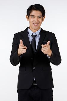 Ritratto di giovane asiatico amichevole ufficiale delle risorse umane in abito formale nero in piedi sorridente sguardo alla telecamera che punta il dito indice da due mani mostrano che vogliamo che tu assuma e assumere lavoratore.