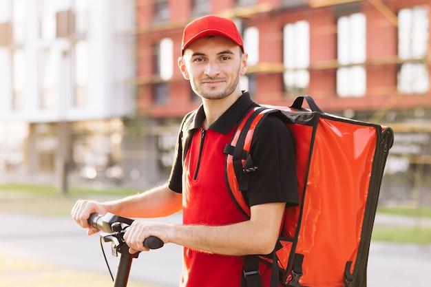 Ritratto di uomo addetto alle consegne in uniforme rossa in piedi in strada e girando il viso verso la telecamera