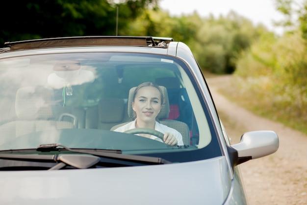 Ritratto sparato attraverso il parabrezza di una bella donna in auto.