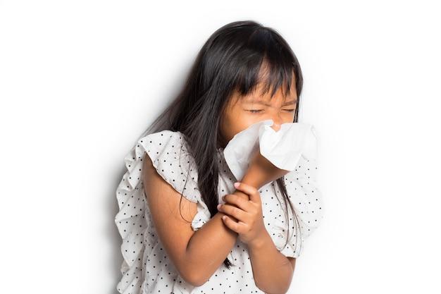 Ritratto della ragazza asiatica malata del bambino piccolo che pulisce e pulisce il naso con il tessuto