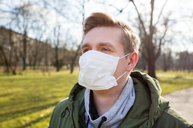 Ritratto di un uomo malato che indossa la mascherina medica su un bacground del parco pubblico della città. pandemia di coronavirus. concetto di inquinamento atmosferico, focolaio di polmonite, smog o epidemia