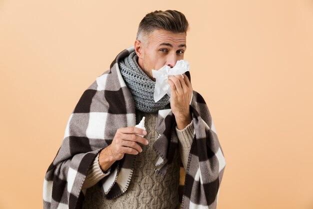 Ritratto di un uomo malato avvolto in una coperta in piedi isolato sopra il muro beige, avendo il naso che cola, usando il tovagliolo