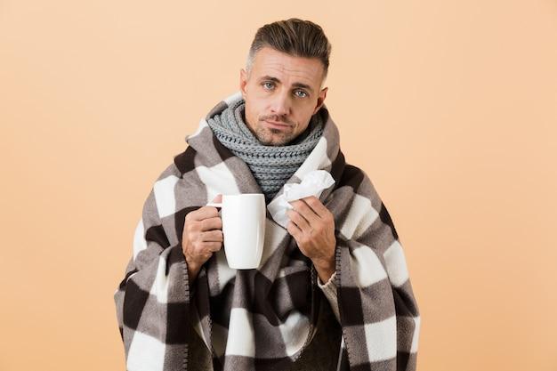 Ritratto di un uomo malato avvolto in una coperta in piedi isolato sopra il muro beige, con in mano una tazza e un tovagliolo