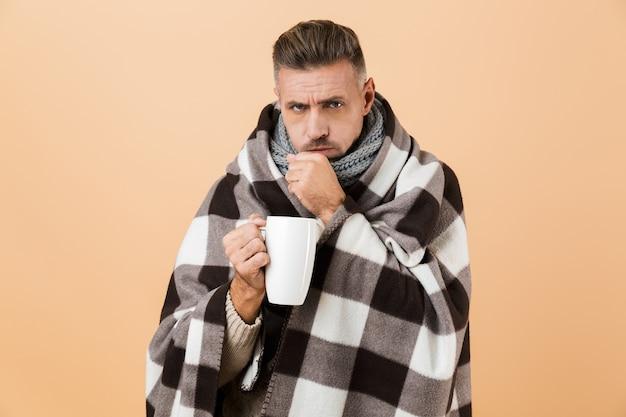 Ritratto di un uomo malato avvolto in una coperta in piedi isolato sopra il muro beige, che tiene tazza con tè caldo