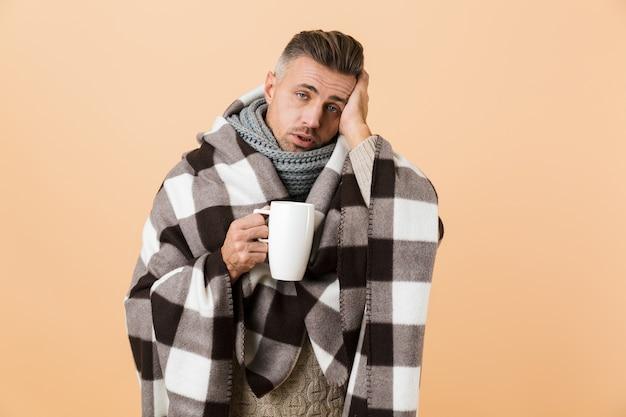 Ritratto di un uomo malato avvolto in una coperta in piedi isolato sopra il muro beige, mostrando il termometro