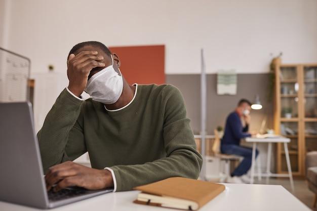 Ritratto di uomo afro-americano malato e stanco che indossa la maschera e utilizzando laptop mentre si lavora alla scrivania in ufficio, copia dello spazio