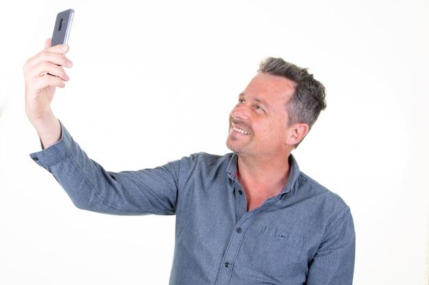 Uomo allegro di profilo laterale del ritratto che prende selfie nel fondo bianco